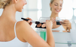 Woman with makeup brush and foundation at bathroom stock photo