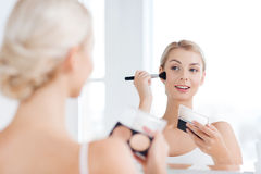 Woman with makeup brush and foundation at bathroom Stock Photos