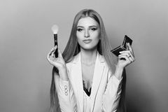 Woman with makeup brush and mirror. Young pretty woman in blue suit holding makeup brush and small mirror and applying cosmetics. Make-up artist. Girl with long Royalty Free Stock Photos
