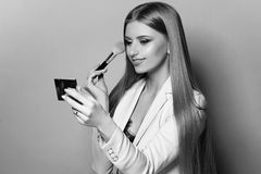 Woman with makeup brush and mirror. Young pretty woman in blue suit holding makeup brush and small mirror and applying cosmetics. Make-up artist. Girl with long Stock Photography