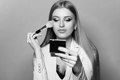 Woman with makeup brush and mirror. Young pretty woman in blue suit holding makeup brush and small mirror and applying cosmetics. Make-up artist. Girl with long Stock Images