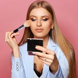 Woman with makeup brush and mirror. Young pretty woman in blue suit holding makeup brush and small mirror and applying cosmetics. Make-up artist. Girl with long Royalty Free Stock Images