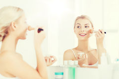 Woman with makeup brush and powder at bathroom Royalty Free Stock Photography