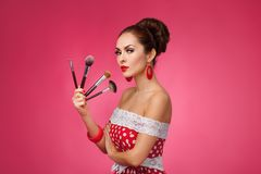 Woman with makeup brushes.   She is standing Stock Image