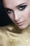 Woman with Makeup and Golden Skin Stock Photo