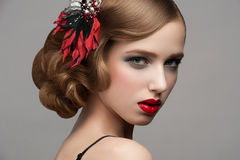 Woman with makeup and hairstyle. Portrait of attractive young woman with red lipstick and  beautiful hairstyle. Hairdo with beautiful hair decoration Stock Image