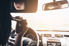 Woman makeup her face using blush brush while driving car Royalty Free Stock Photos