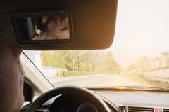 Woman makeup her face using blush brush while driving car Stock Photos