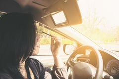 Woman makeup her face using eyebrow pencil while driving car. Unsafe behavior stock photos