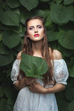 Woman with makeup in nature. Portrait of a young woman with a delicate make-up among the green leaves Stock Photo