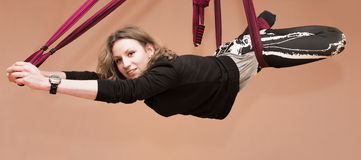 Woman making aerial yoga exercises, indoor Royalty Free Stock Images