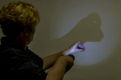 Woman making animal shadow figure. Woman using flashlight to make animal shadow figure of duck on white wall Stock Photo