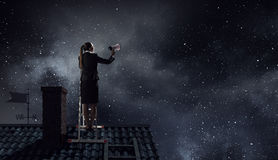 Woman making announcement in megaphone . Mixed media. Businesswoman standing on ladder high and shout in megaphone Stock Photos