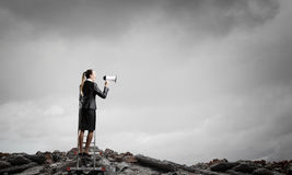 Woman making announcement in megaphone . Mixed media. Businesswoman standing on ladder high and shout in megaphone Stock Images