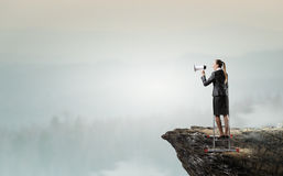 Woman making announcement in megaphone . Mixed media. Businesswoman standing on ladder high and shout in megaphone Royalty Free Stock Photography