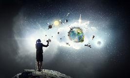 Woman making announcement in megaphone . Mixed media. Businesswoman standing on ladder high and shout in megaphone. Elements of this image are furnished by NASA Royalty Free Stock Photography