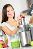 Woman making apple and vegetable juice on juicer. Machine at home in kitchen. Juicing and healthy eating happy woman making green vegetable and fruit juice royalty free stock photography