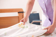 Woman making bed Royalty Free Stock Image