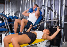 Woman making bench press exercise from supine position using gym Stock Image