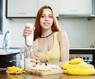 Woman making beverages  from bananas and milk. Positive woman making beverages with blender from bananas and milk Royalty Free Stock Photo