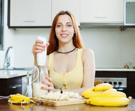 Woman making beverages with blender from bananas Royalty Free Stock Photo