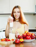 Woman making beverages with  blender from nectarines Stock Images
