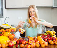 Woman making beverages from fruits Stock Photography