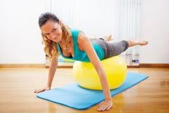 Woman making body exercises on a yellow ball Royalty Free Stock Photos