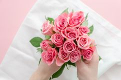 Woman making bouquet of pink rose. Girl holds a bouquet of flowers. Flower shop. Florist at work nosegay arrangement. Woman making bouquet of pink rose. Girl stock image