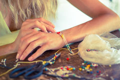 Woman making bracelet at home Stock Image