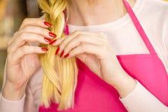 Woman making braid on blonde hair royalty free stock images