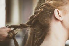 Woman making braids at hair studio royalty free stock photo