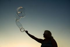 Woman making bubbles. For the amusement of her daughter in the setting sun Stock Image