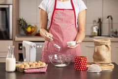 Woman making a cake. Detail of female hands adding flour into a mixing bowl while making a cake royalty free stock photos