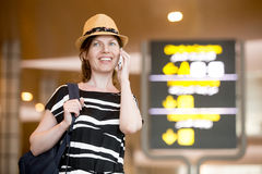 Woman making call in front of information board in airport Stock Images