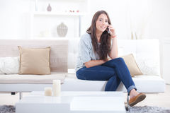 Woman making call whilst on sofa Royalty Free Stock Photo