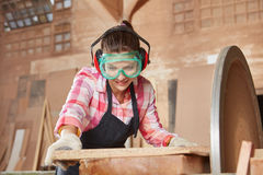 Woman making carpenter apprenticeship. And working with grinder stock photography