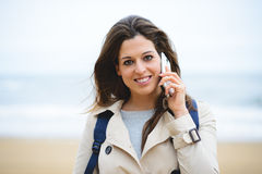 Woman making cellphone call on winter trip to the beach Royalty Free Stock Photography