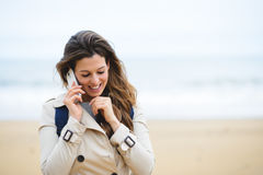Woman making cellphone call on winter trip to the beach Stock Photography