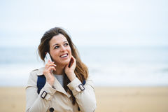 Woman making cellphone call on winter trip to the beach Stock Image