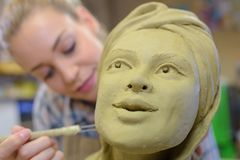 Woman making ceramic face in art class. Woman making ceramic face in an art class royalty free stock images