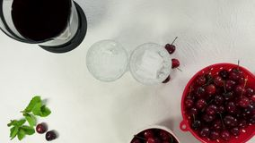 Glasses of cherry juice with ice and mint, preparation process. Cherries in a bowl, on a kitchen table in white background, top vi stock video