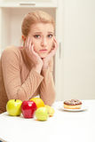 Woman making choice between fruit and donut stock image