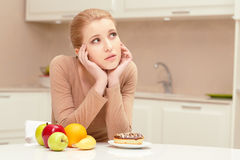 Woman making choice between fruit and donut Stock Photography