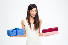 Woman making choice between two gift boxes. Chatming woman making choice between two gift boxes isolated on a white background Stock Photo