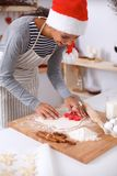 Woman making christmas cookies in the kitchen Royalty Free Stock Images