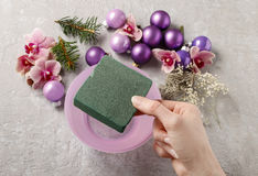 Woman making christmas decorations with violet balls, fir and or Royalty Free Stock Photo