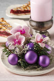 Woman making christmas decorations with violet balls, fir and or Royalty Free Stock Image