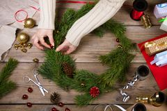 Woman making Christmas wreath. Top view. Woman is making Christmas wreath. Top view stock image