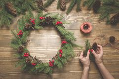 Woman making Christmas wreath using fresh and all natural materials. Flat lay. Top view. royalty free stock photography